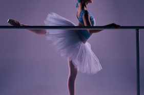 39081577 - classic ballet dancer in white tutu posing on one leg at ballet barre on a lilac background