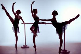 40507303 - three young ballerinas stretching on the bar on lilac background