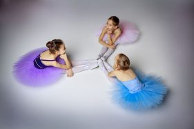 47799489 - three little ballet girls sitting  in multicolored tutus and pointe shoes together on lilac background
